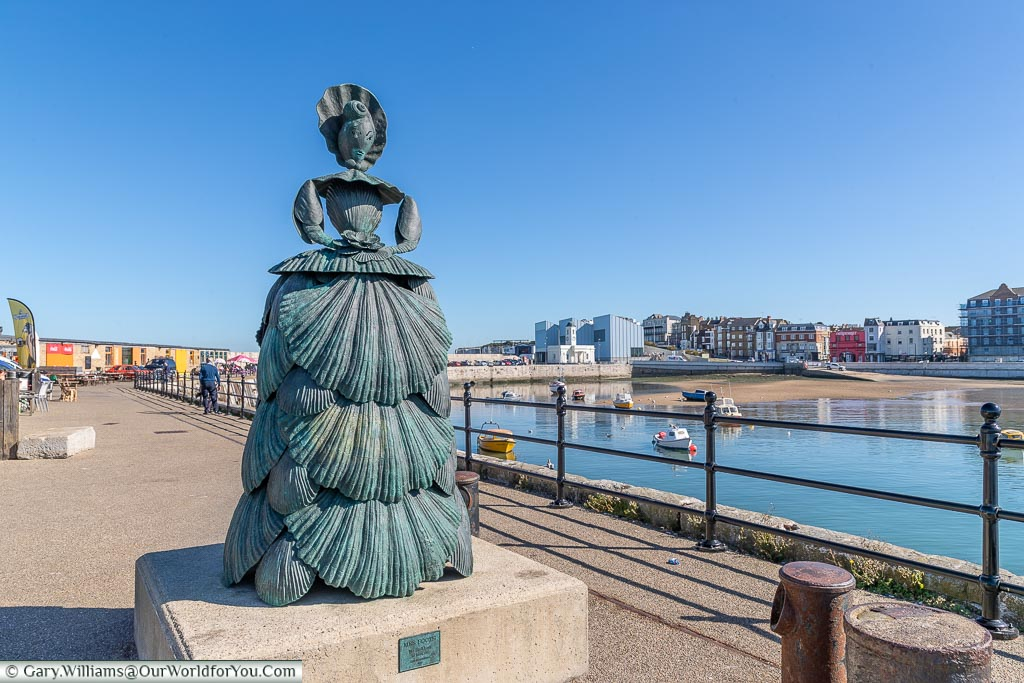 A bronze statue of a woman made of shells, known as 'The Shell Lady of Margate' by Ann Carrington at the end of the Harbour Arm in Margate's Old Town.