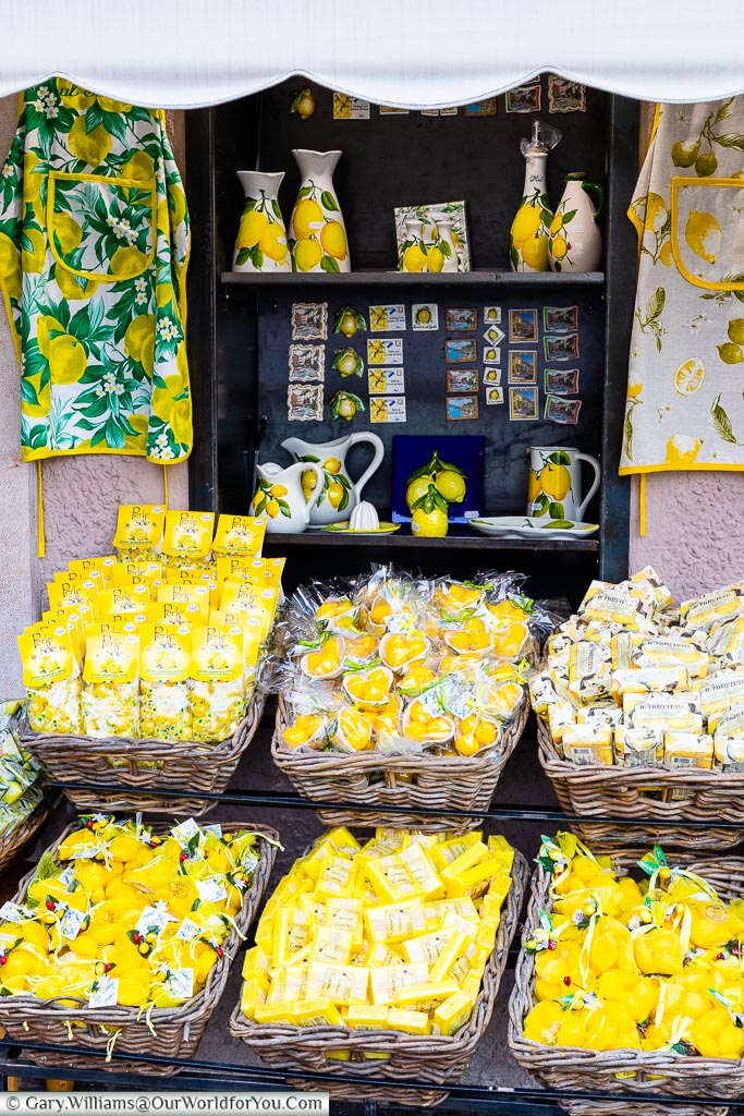 The display outside a shop with baskets of Lemon soaps, bath bombs, lemon sweets  & other lemon based products.  On the shelves behind are jugs, olive oil poured, fridge magnets all decorated with lemons.