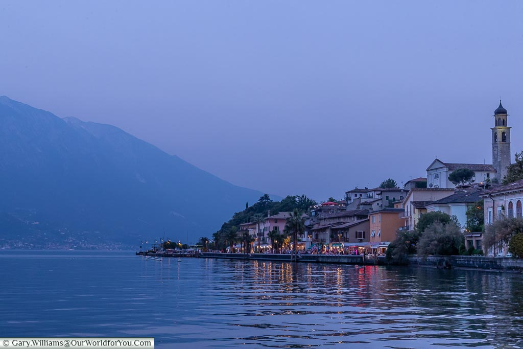 A view of Lake Garda at dusk with the town on the right, and the mountains on the left.
