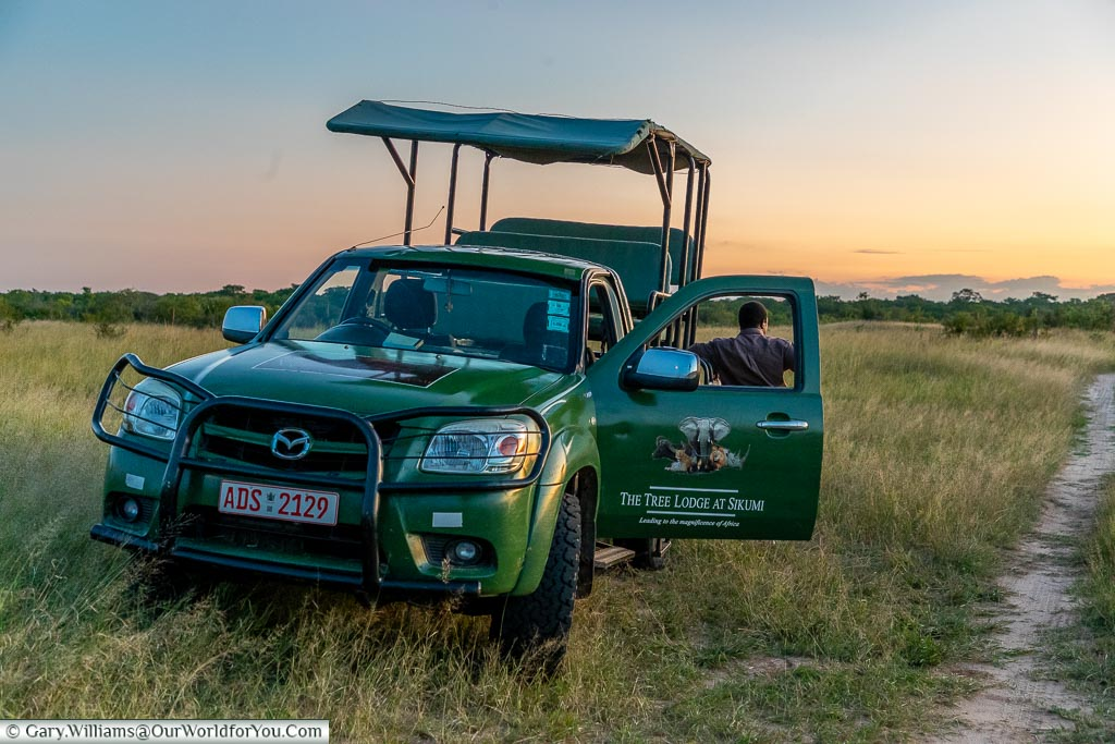 The safari truck parked up with its door open just at the edge of a track as the sun goes down.