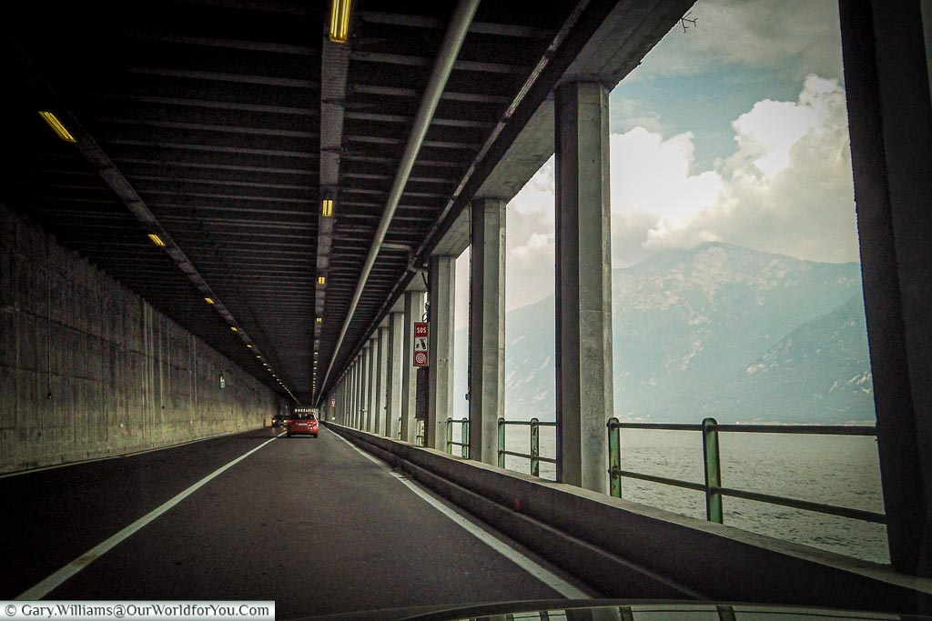A dashboard view of the road inside one of the tunnels alongside the north of Lake Garda - to the right are columns with a view across the lake and the mountains of the far side.