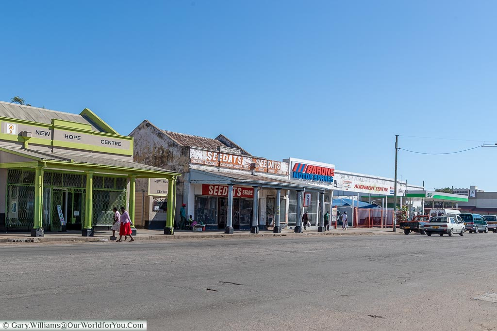 A street scene of a wide road and shops that have seen better days.