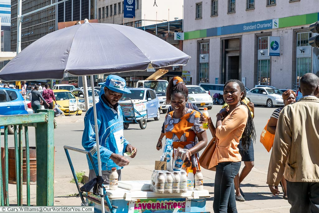Two local women buying drinks from a street vendor in the centre of Harare.