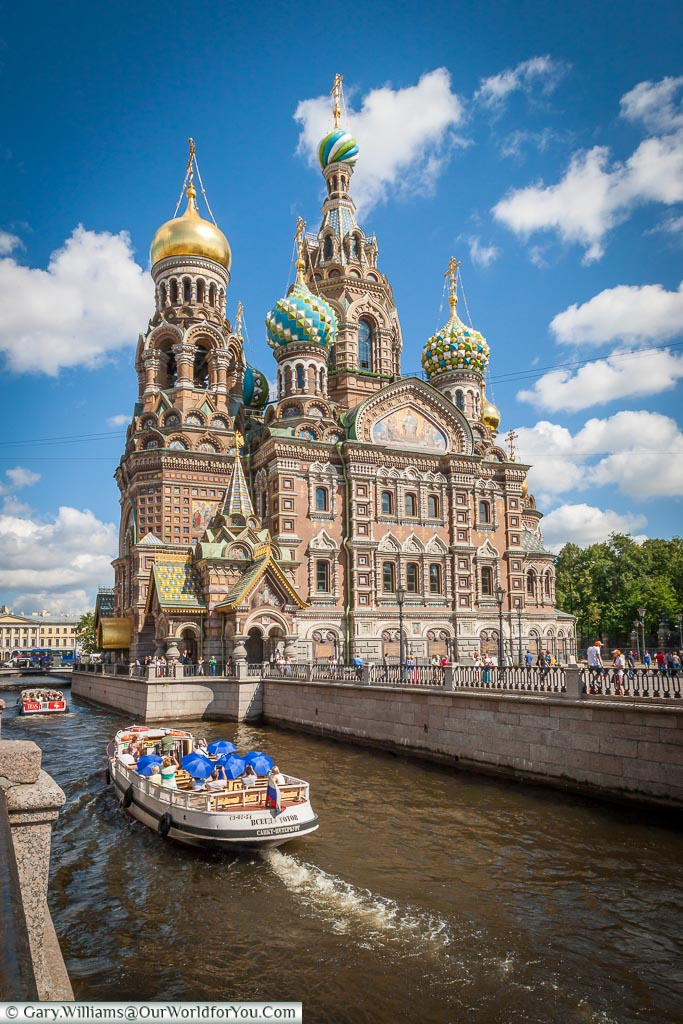 A pleasure boat passes by the Church of the Savior on Spilled Blood on the Moyka River in Saint Petersburg, Russia