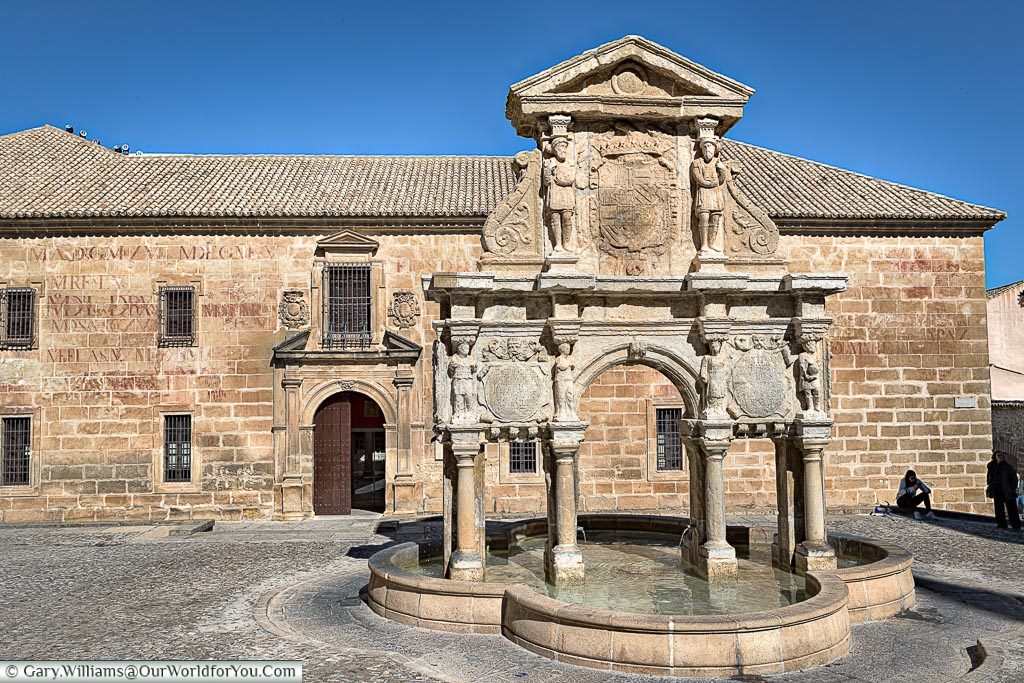 In front of a historic stone fountain in Baeza.
