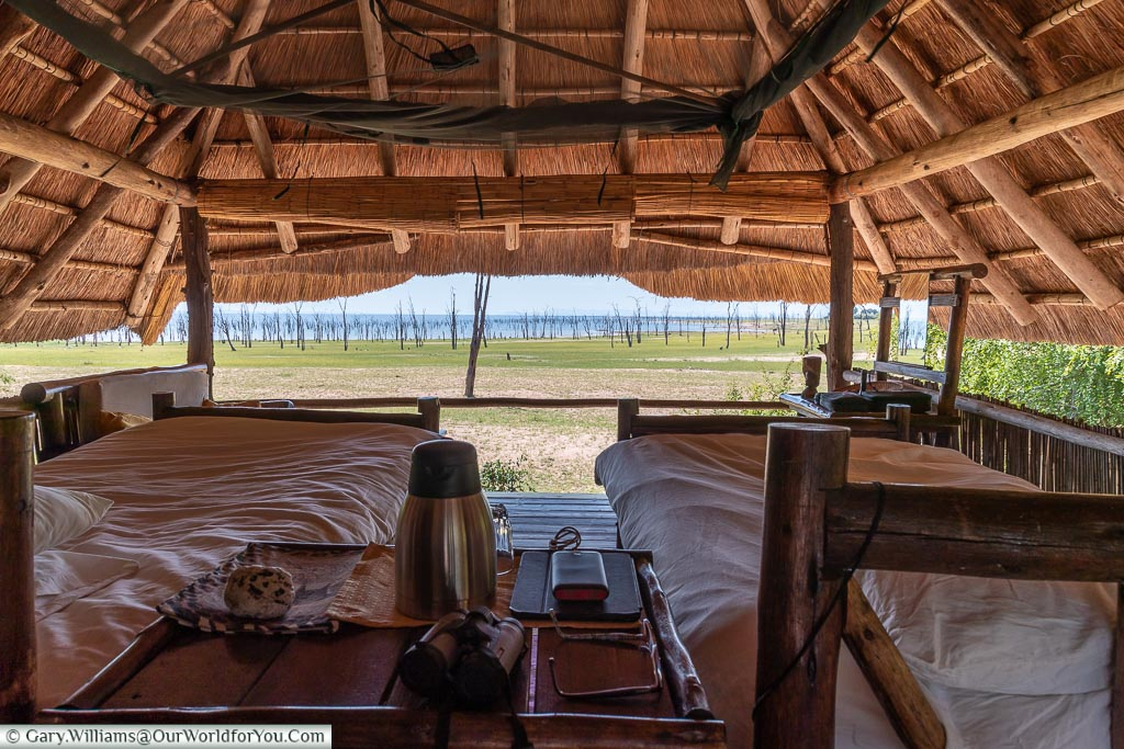The windlowess interior of the lodge under a thatched roof with a view over Lake Kariba