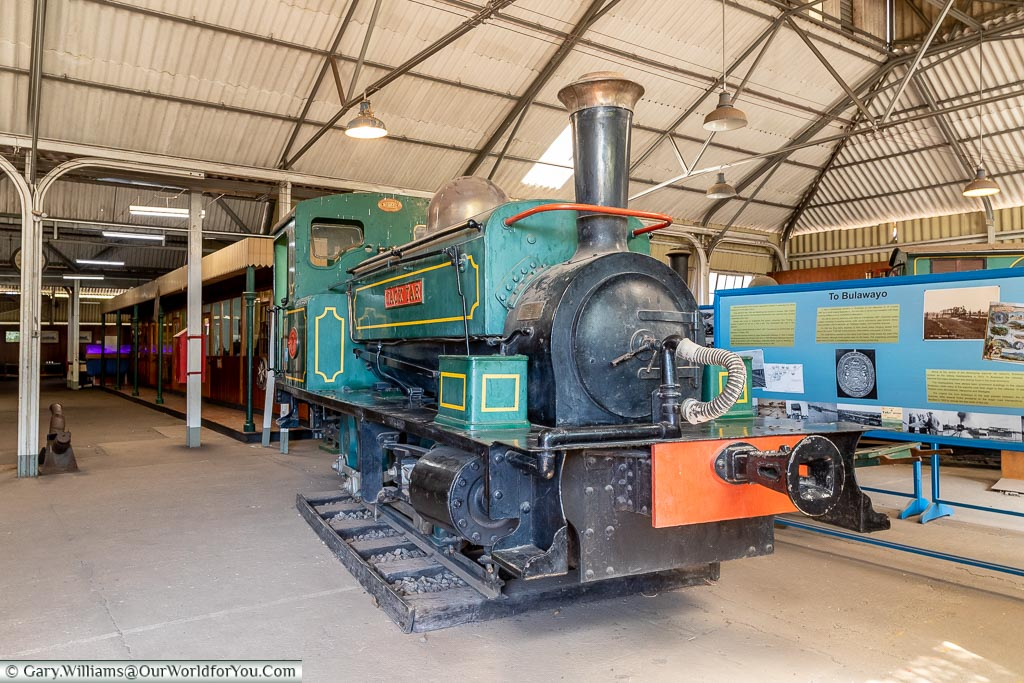 A restored small steam locomotive, predominately green with yellow trim, called the Jack Tar.