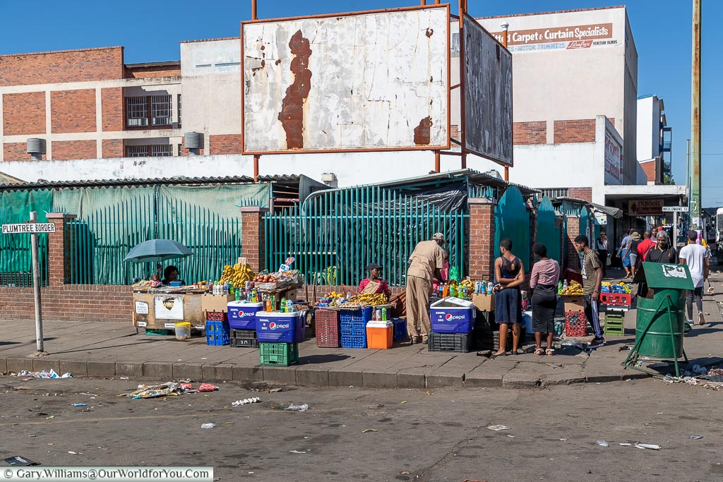 A bustling street corner in Bulawayo where a few stalls have been set up on plastic creates selling fruit and vegetables.