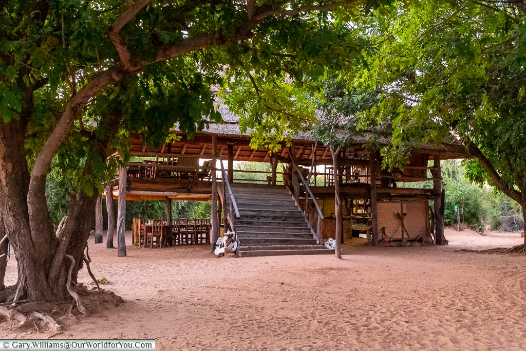 The two-storey boma, an open-air gathering place with a thatched room.  The Boma is free standing in a small clearing in a wooded area.