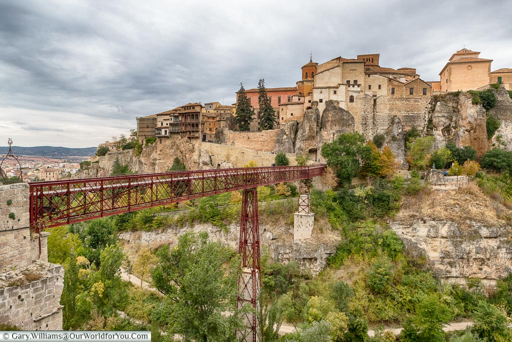A red iron bridge across the gorge to the old town of Cuenca.