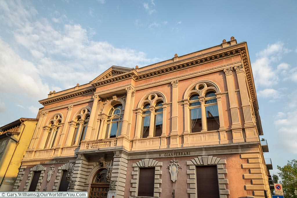 The exterior of a neoclassic building the houses the Trento Philharmonic.