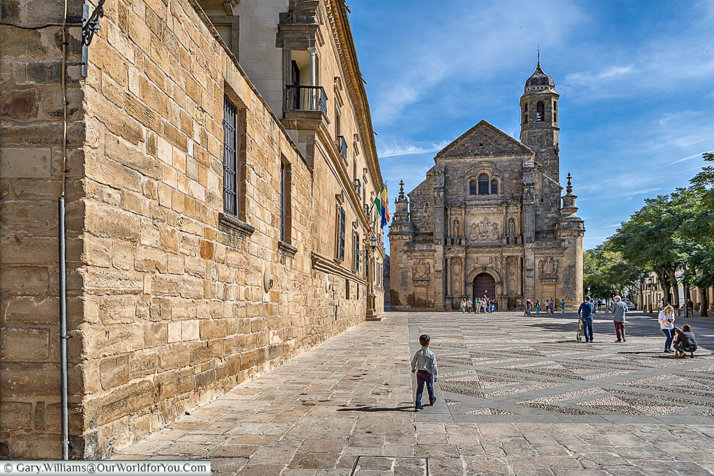 A small child walking across the courtyard in front of the Sacra Capilla del Salvador.