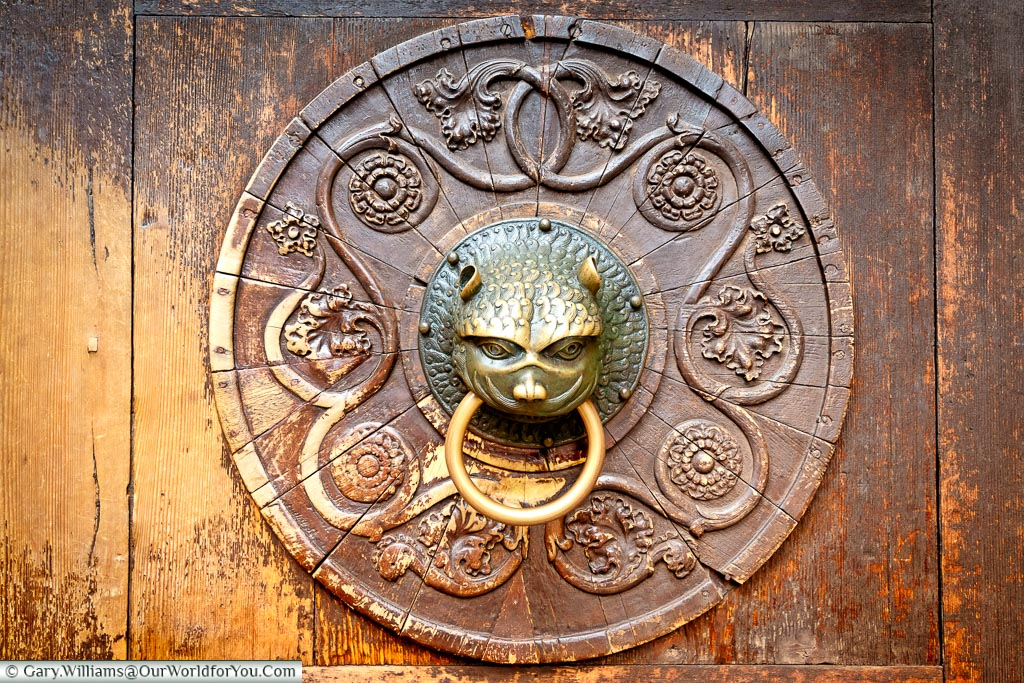An ornate brass door knocker on the entrance to Augsburg Cathedral.