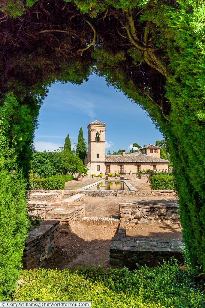 A view through a hedge to the Parador de Granada.