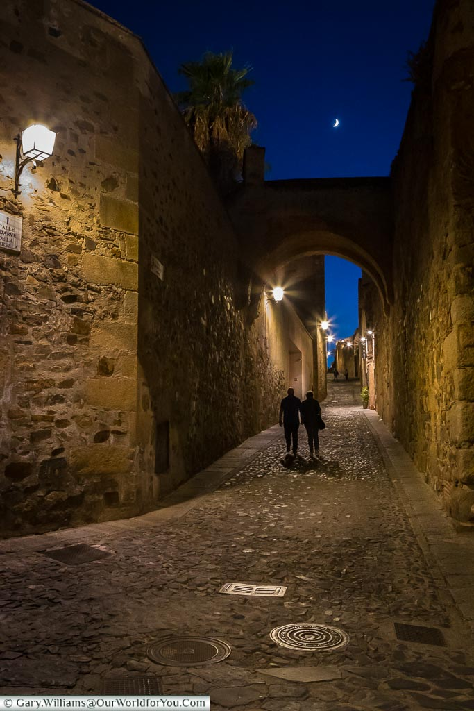 A couple walking a quiet lane in Cáceres lit by lanterns .