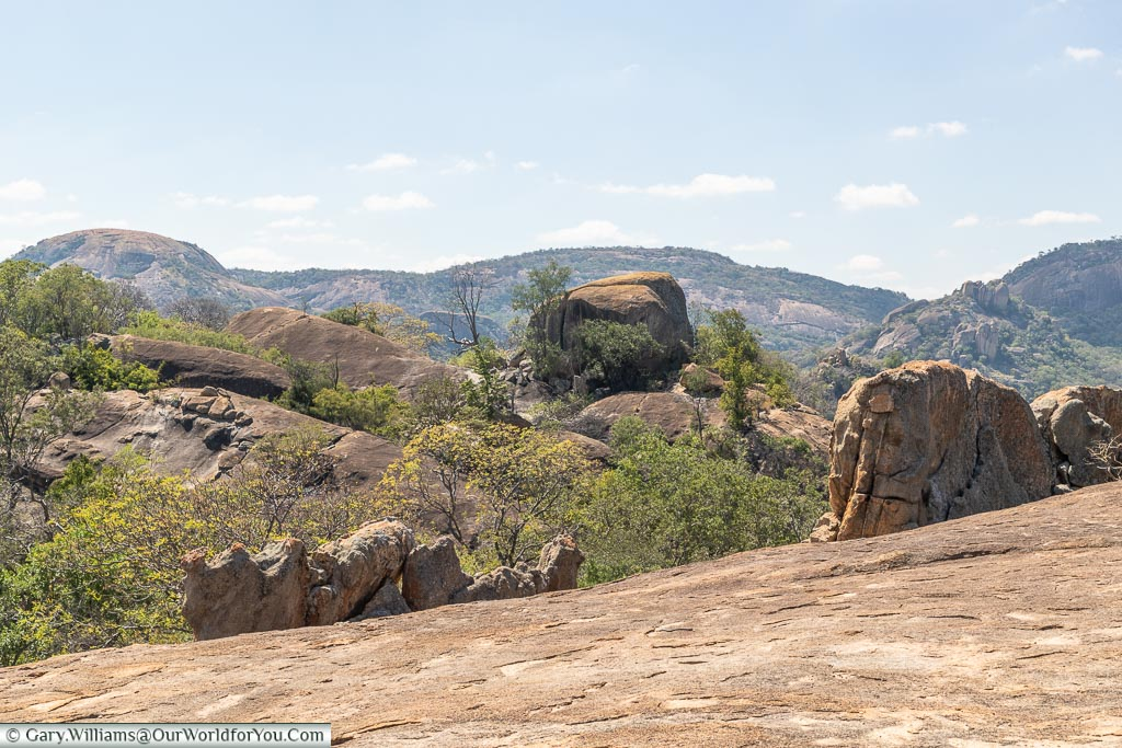 A view of a collection of boulders from the top of another rock formation.