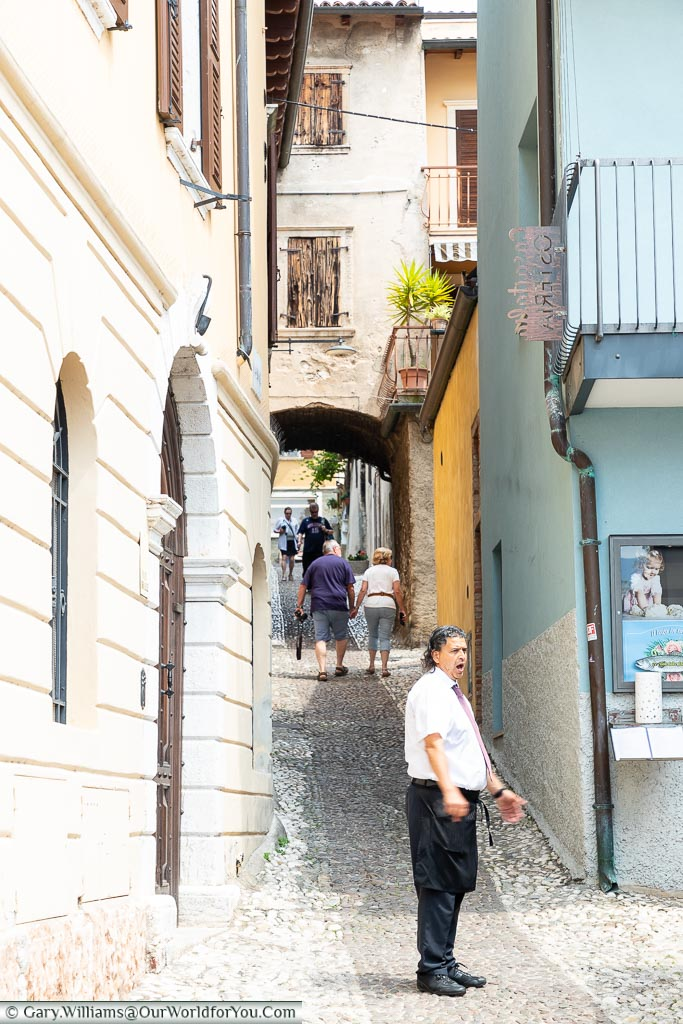 A narrow lane is heading away from the lakeside uphill.  At the base of the hill is a waiter trying to drum up trade for his restaurant.