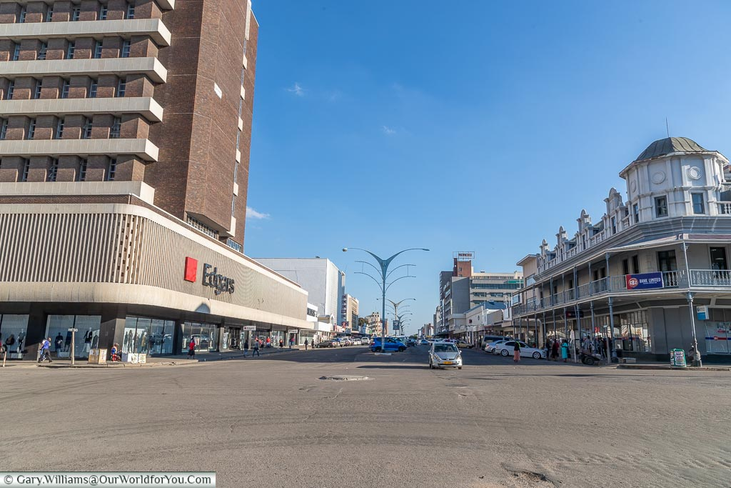 A look along a wide road through central Bulawayo with modern building on the left and colonial-era buildings on the right.