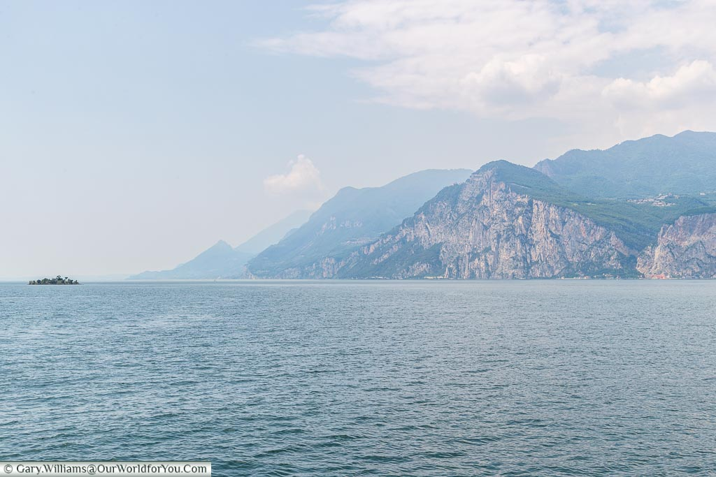 A view of Lake Garda, the mountains on one side, taken whilst crossing on a ferry towards Malcesine.