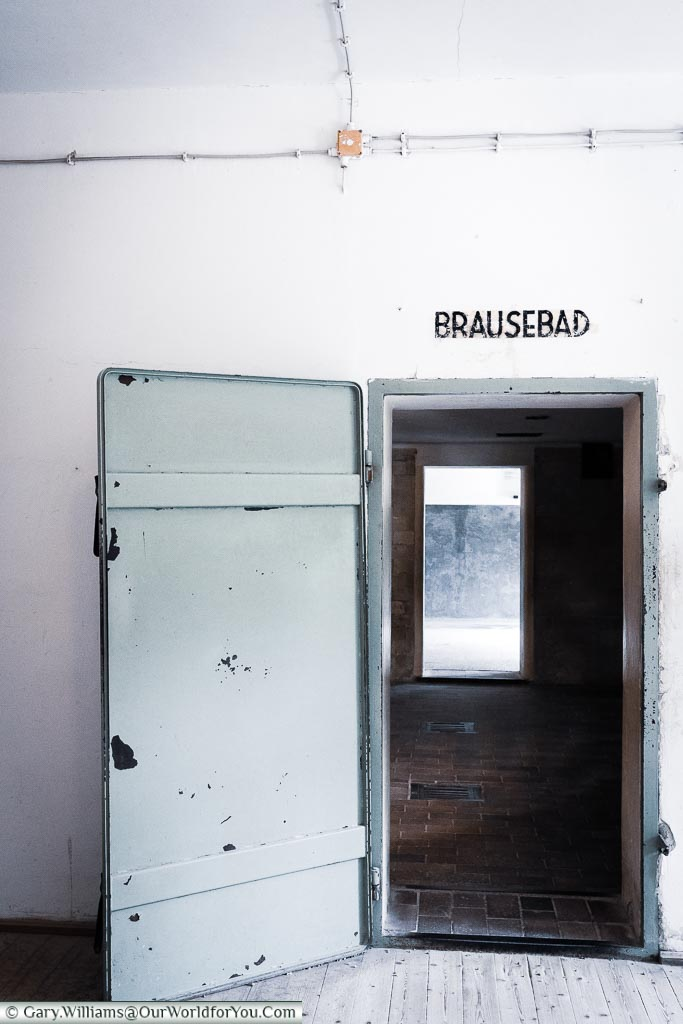 An iron door that led to the gas chamber the camp. Above the door is a sign for Brausebad - Shower/Bath.