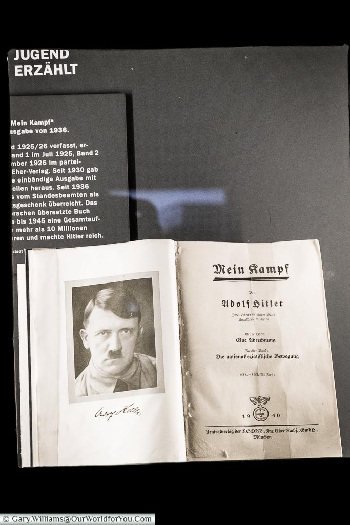 A museum exhibit of Mein Kampf open to the title page with a portrait of Adolf Hitler.