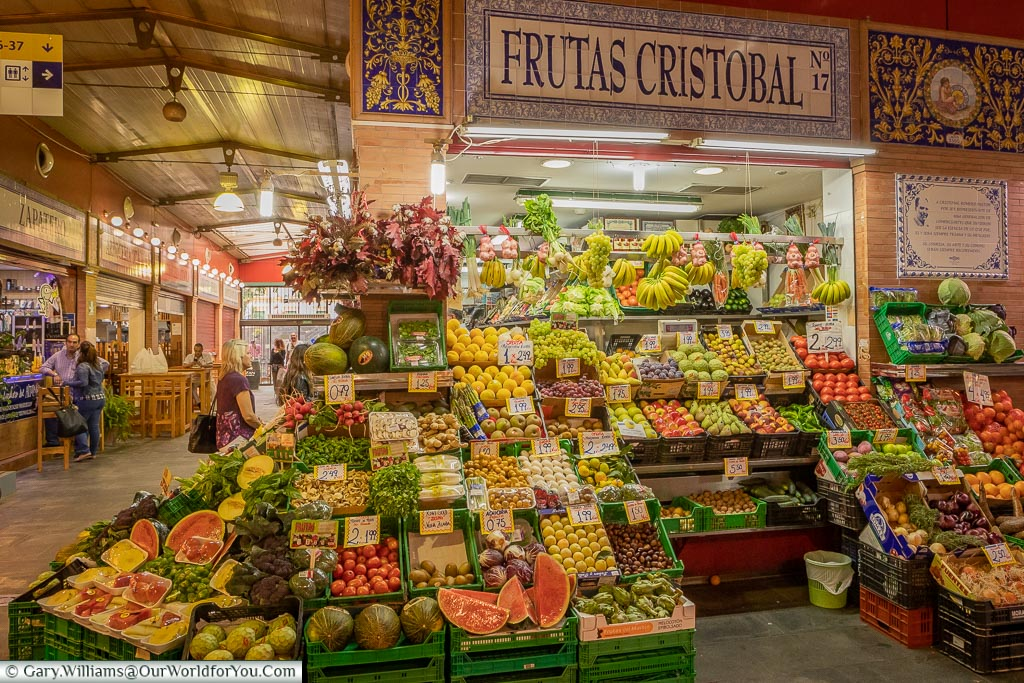 Inside the Mercado de Triana.  A vendors booth, decorated with traditional tiles of the region, is piled high with fruit and vegetables.