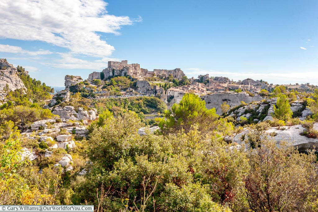 A view in the distance of the hillside town of Les Baux-de-Provence with the remains of its historic ruins atop the craggy rockfac