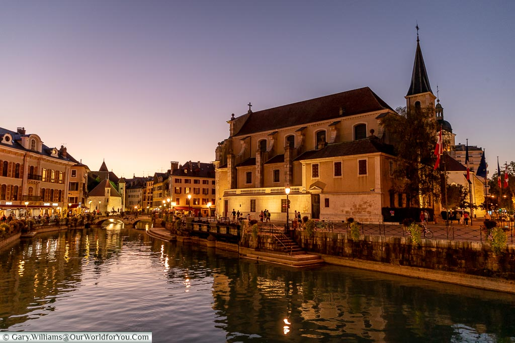 A view over the canal fed off Lake Annecy at dusk with the church of Saint-François de Sales dominating the skyline.