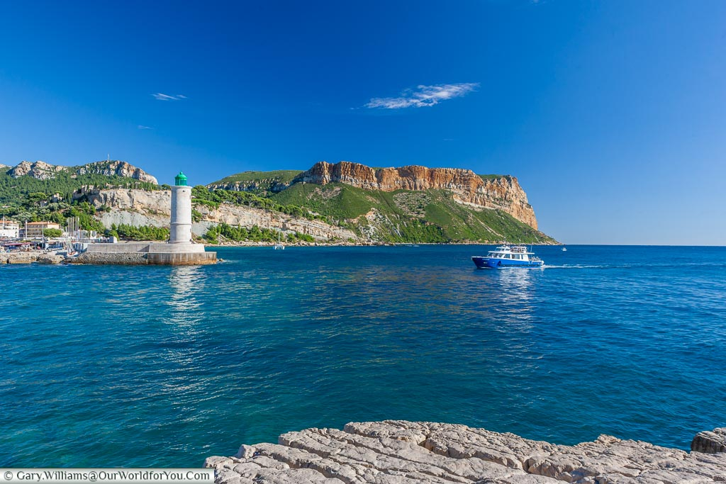 Standing on the rocky shore looking at a small pleasure boat returning the harbour of Cassis. A little stone lighthouse stands on the side of the harbour wall.