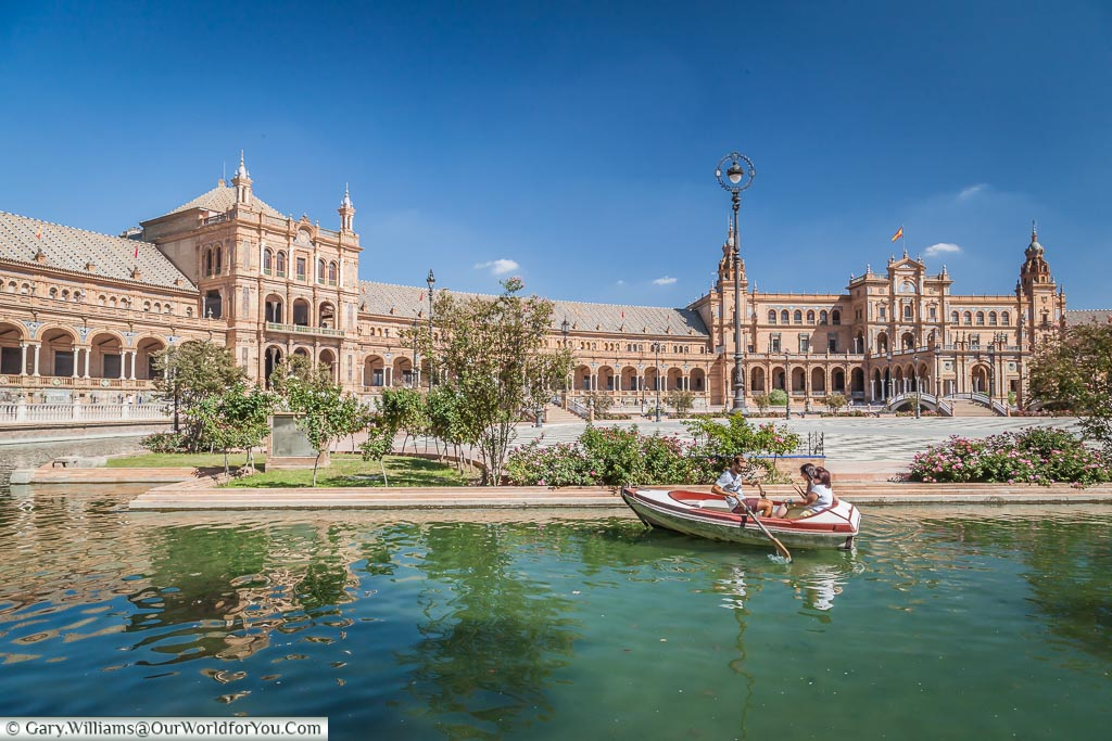 A family of three in a small rowing boat enjoy the boating lake in the Plaza Plaza de España.  The neo-classical complex built for the 1929 Ibero-American Exposition.