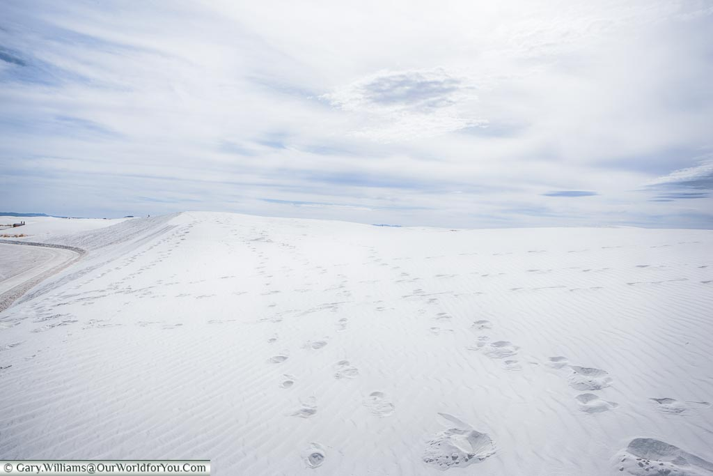 Footprints in the white sand that looks just like snow.