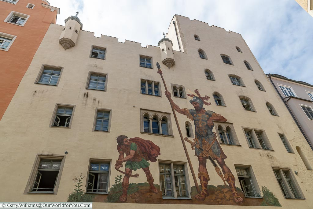 A mural of David & Goliath, over 3 storeys high, on the side of a sand-coloured building.