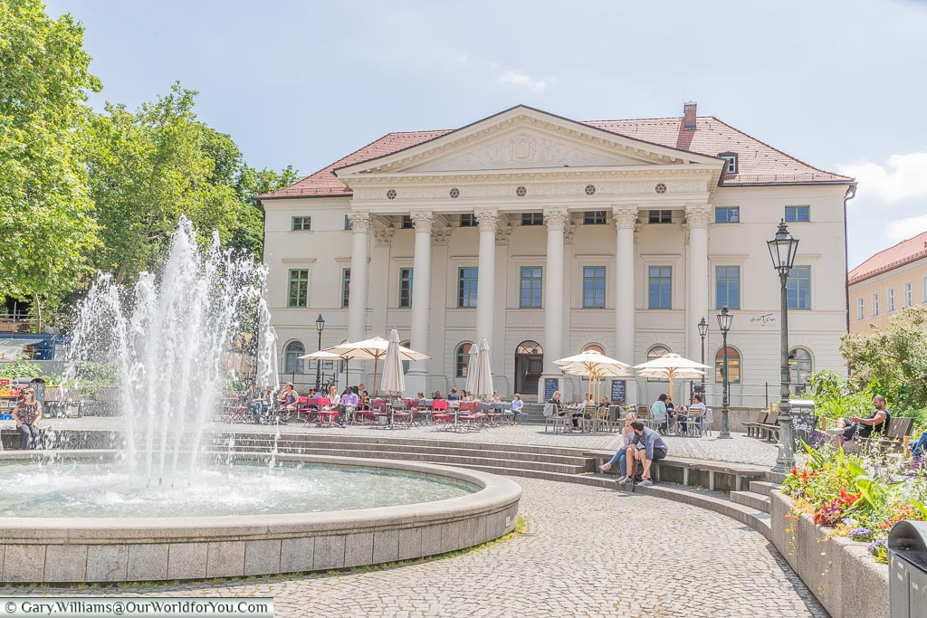 A fountain in a square in front of a neoclassical building that is now home to a music school.