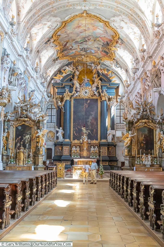 The view along the nave of Saint Emmeram's Abbey in a Rococo style with ornate detailing of the walls & ceiling.