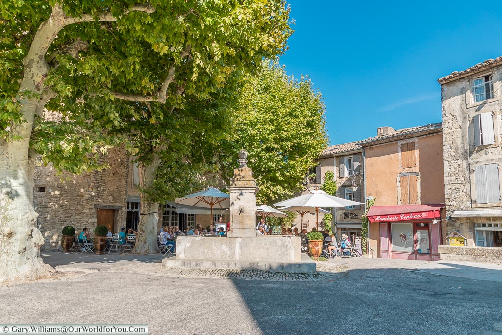 A fountain in a square with dinners enjoying lunch under the shade of trees.
