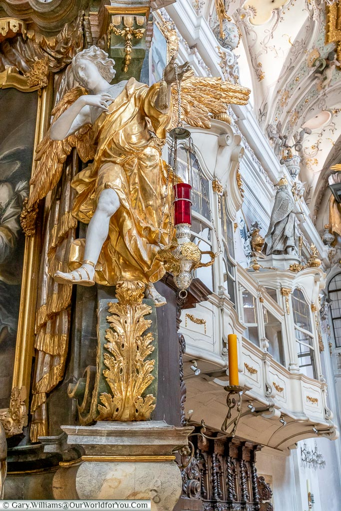 A close up of the detail inside Saint Emmeram's Abbey focusing on an angel lavishly wrapped in a gold tunic with golden wings.