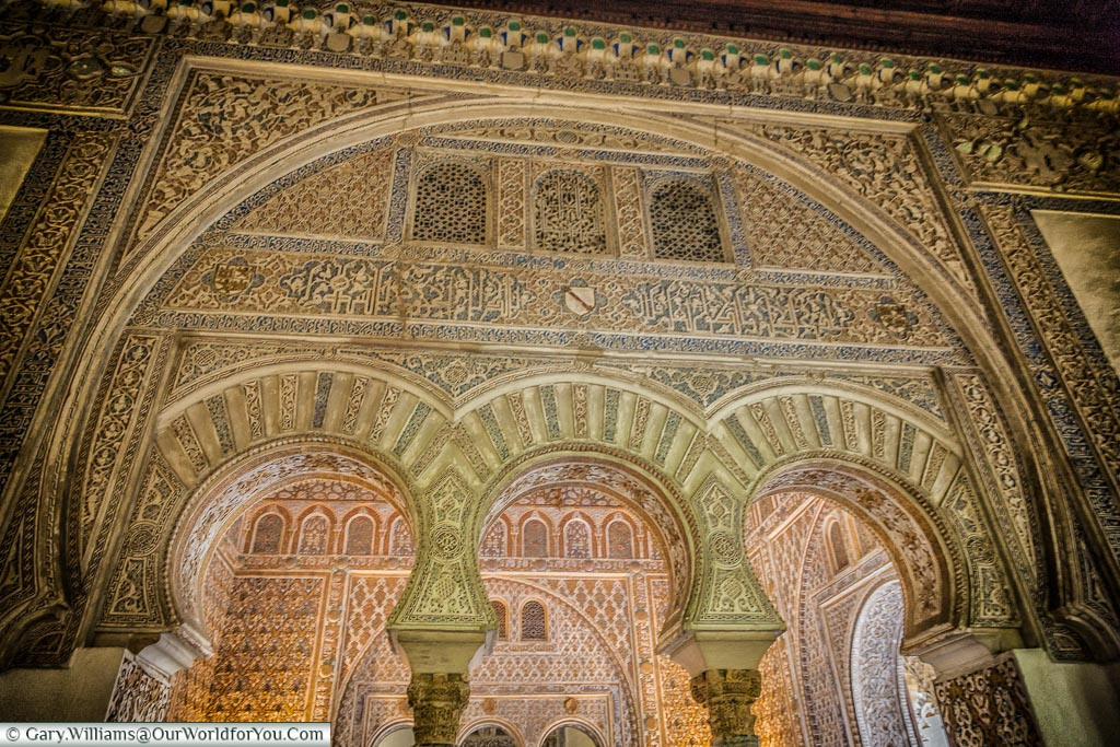 A closeup look through one ornately decorated Moorish arch, to a room as equally ornate inside Seville's Alcazar.