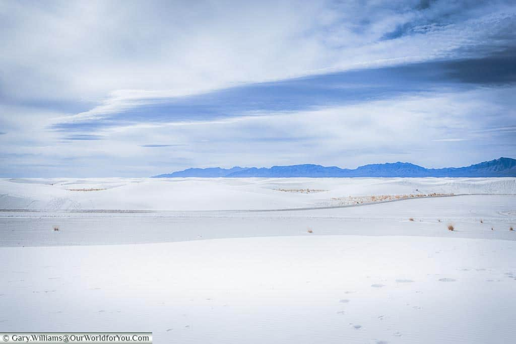 Dark mountains in the distance add contrast to the all-white scene across the White Sands National Monument.