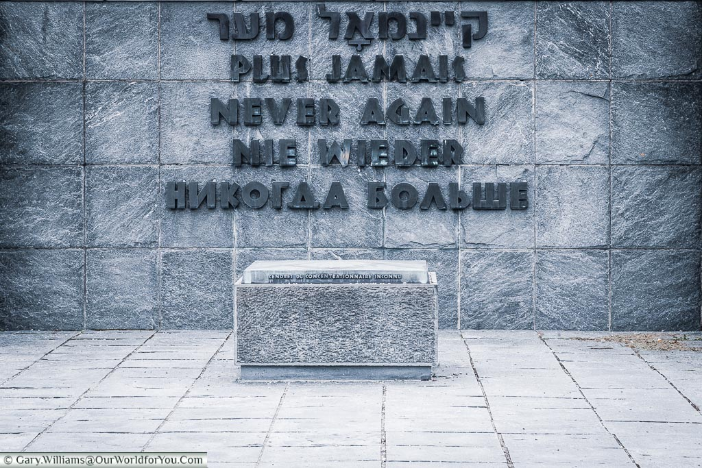 A square memorial containing recovered ashes of victims of the camp in front of a wall with 'Never Again' inscribed in Hebrew, French, English, German & Russian.