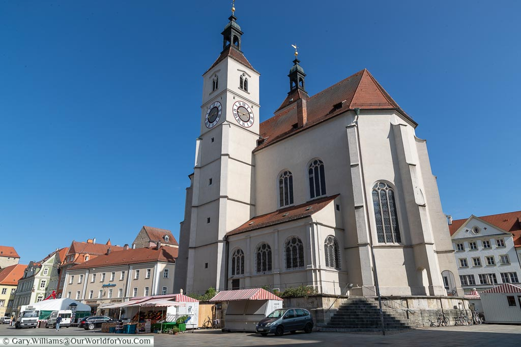 A large church with a clock tower and a few market stalls in front.