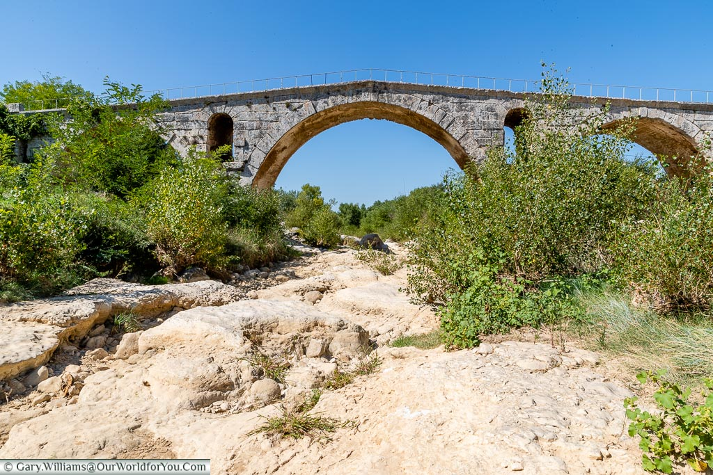 The small Roman bridge over a dry riverbed against a clear blue sky.