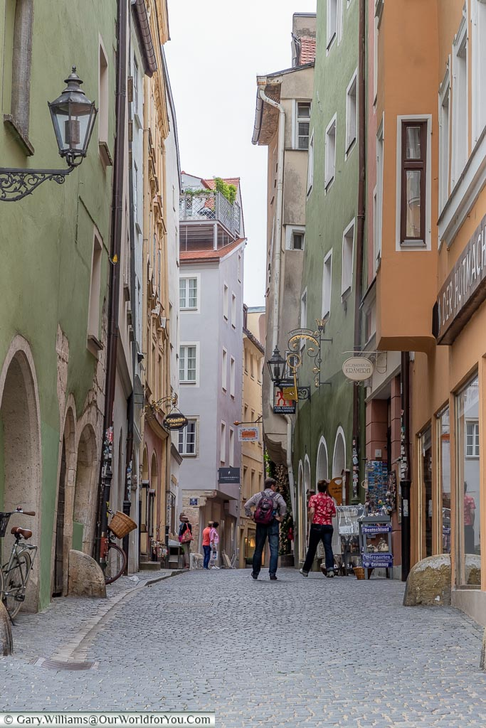 A narrow cobbled street view in the old town of Regensburg lined with shops.