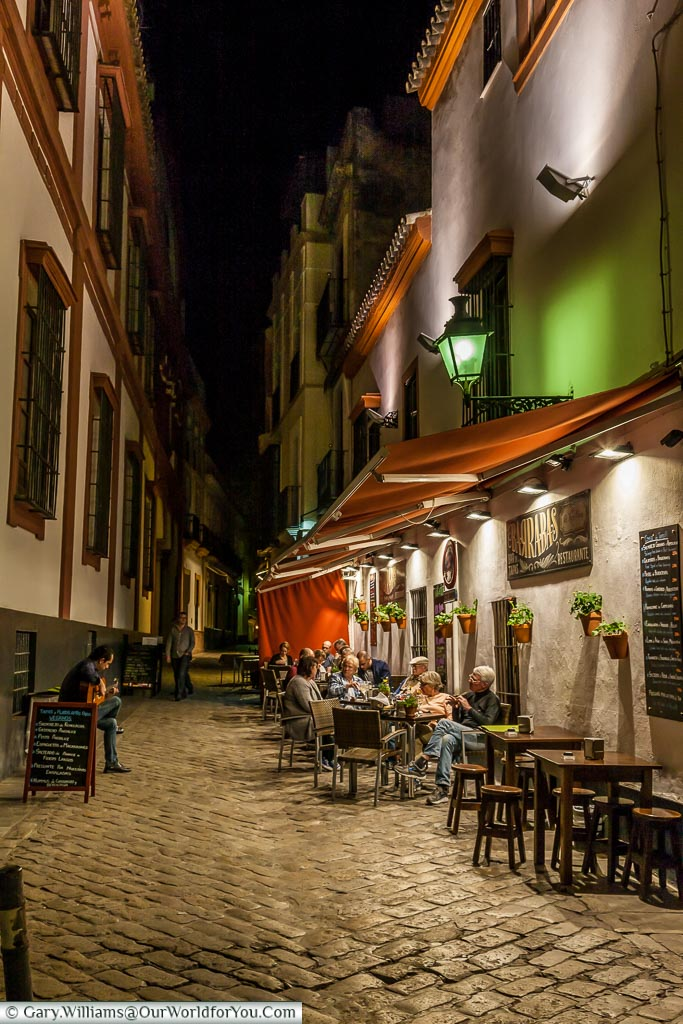 A musician plays a Spanish guitar, in a narrow cobbled lane, in front of a group of people sitting outside a restaurant at night in the Barrio Santa Cruz area of Seville.