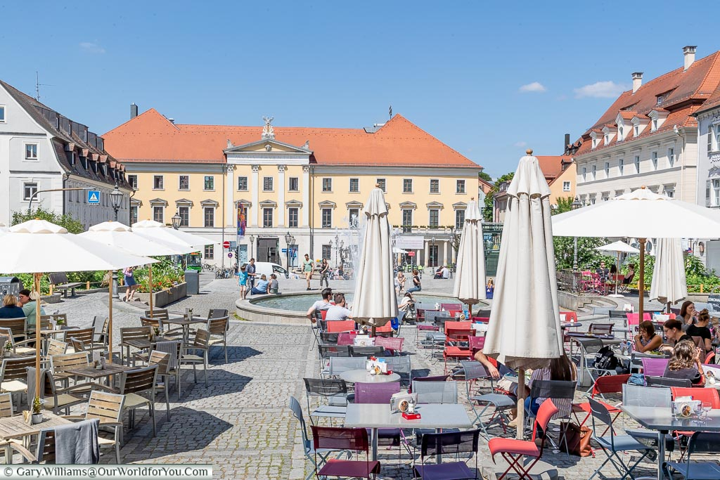 A view over tables and chairs of a cafe in Bismarkplatz to the fountain and theatre beyond
