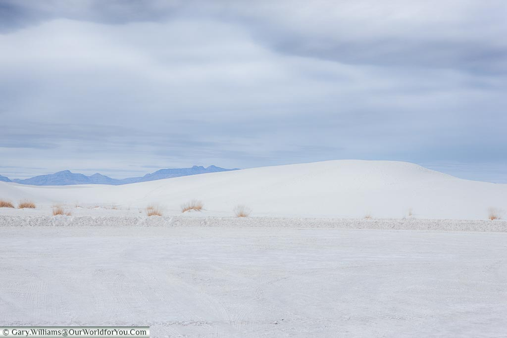An almost white landscape as you look across a white plateau to a white dune in the middle distance, only the darket mountains in the distance give a little contrast.