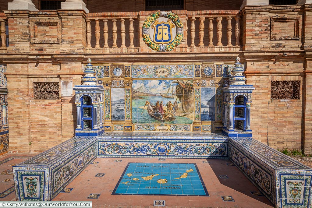 One of the features of the Plaza de España in Seville is the tiled alcoves for each of the regions of Spain.  This is the one for the Canaries.  The primary colours of the tiles are blue & yellow with a scene depicting from the area taking centre spot.