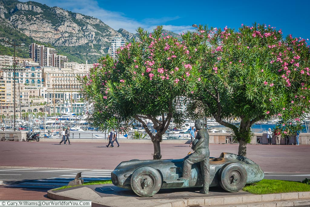 A bronze statue of a facing driver standing next to his 1950's formula 1 car under a couple of trees in flower, in front of the famous Monaco harbour.