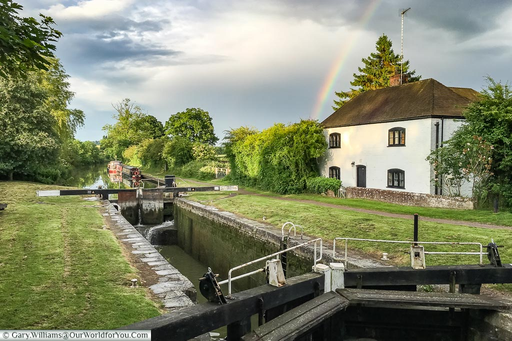 The old Lock Keepers house with a rainbow over it.  In the distance is our wide beam canal boat just past the locks in the foreground.