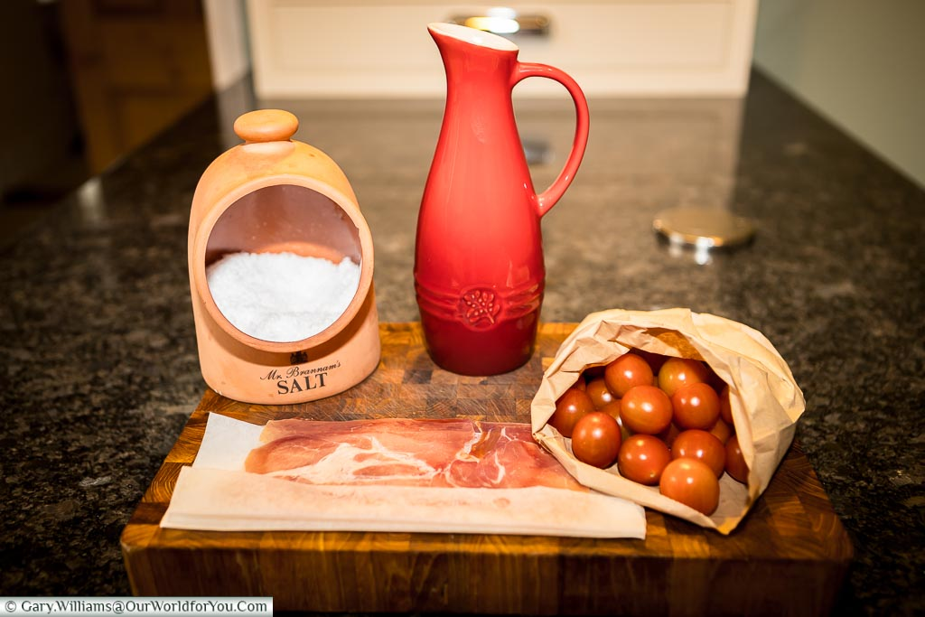 The basic ingredients for a Pan con Tomate, a salt pig filled with Maldon sea salt, a jug full of olive oil, a paper bag full of cherry tomates and some serrano ham wrapped in brown paper on a wooden chopping board.