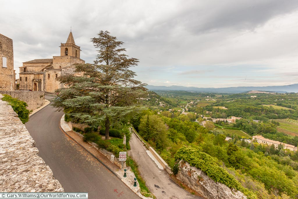 A view of the Provence landscape to the right with a road on the left leading up to the small stone church of Venasque.